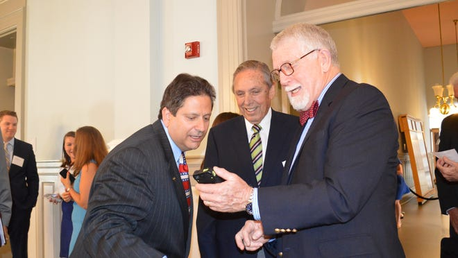 """Former Gov. Bob Martinez and Florida TaxWatch president Dominic Calabro, left, look at pictures on the cell phone of his former chief of staff, John """"Mac"""" Stipanovich, at the Old Capitol on Tuesday."""
