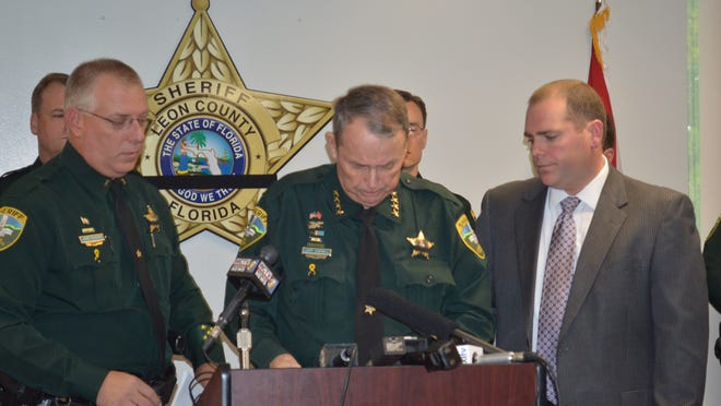 Sheriff Larry Campbell is overcome by emotion Sunday while discussing the fatal shooting of Deputy Christopher L. Smith. Lt. James McQuaig and the sheriff's son, Assistant State Attorney Jack Campbell, stepped forward to show their support.