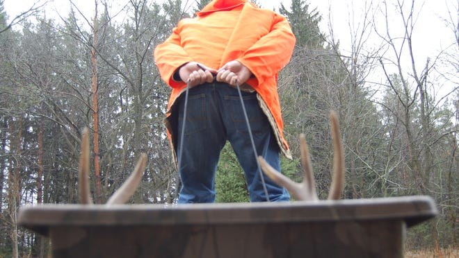 Columnist Doug Berdan drags a deer out of the woods after a successful hunt.