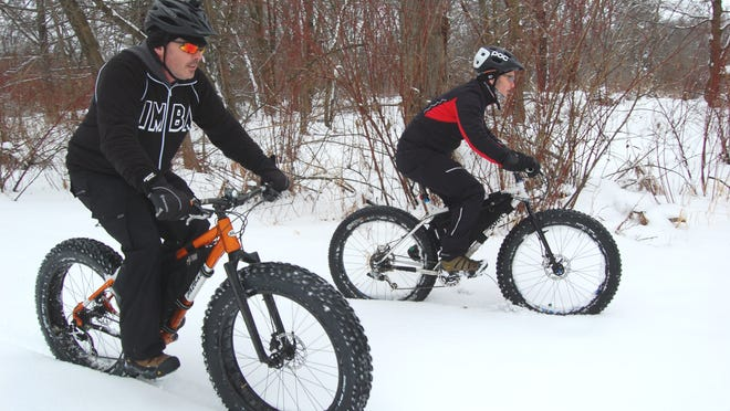 Bob Dunahee, left, and Gary Barden ride their fat bikes at Oak Island Park.
