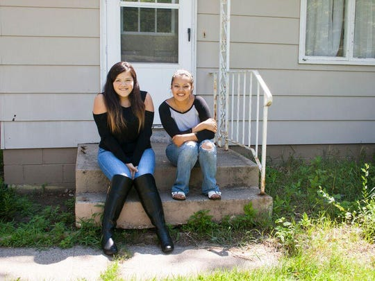 Alondra Hernandez, 17, left, and Ixayana Gonzales, 19, are sisters who find themselves living in two cultures — the Hispanic world of their parents and the American culture they were born into. They are shown at their St. Cloud home July 21.