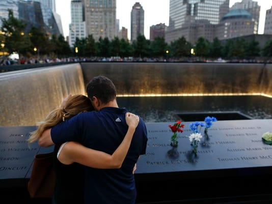 In this Sept. 11, 2014 file photo, David Pykon, right, and his fiancé Shelli Scrimale embrace while observing the 13th anniversary of the attacks on the World Trade Center at the north pool of the memorial in New York. (AP Photo/Julie Jacobson, File)