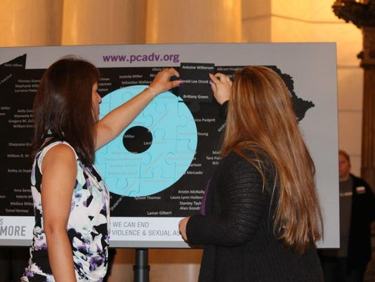 Karen Kuykendall Nordsick (at left) and Becky Schrum (at right) place the final puzzle piece at a ceremony Tuesday, Oct. 13, 2015, to honor domestic homicide victims. The annual ceremony is presented by the Pennsylvania Coalition Against Domestic Violence.