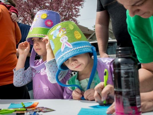 Cleo Orndoff left, and Camryn Orndorff wear Easter buckets on their heads while their parents sign forms for prize drawings before an Easter egg hunt last year.