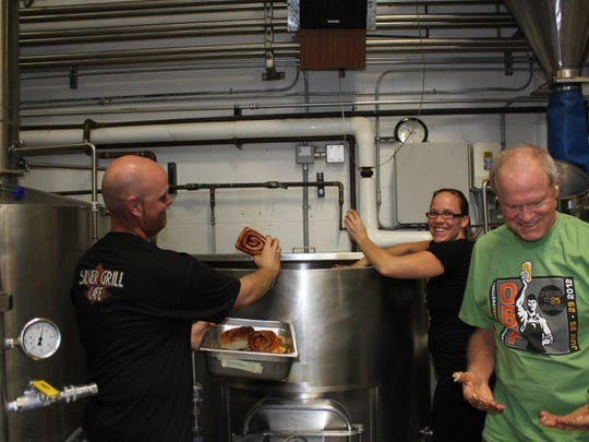 Brewery founder Doug Odell looks at his icing-covered hands as Silver Grill Cafe managing partners Heather and Ian Beckman add more cinnamon rolls to a batch of CinnsationAle.