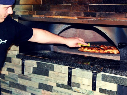 A pizza goes into the oven at 7 Stone pizzaria in West Des Moines. The business opened in April, 2015.