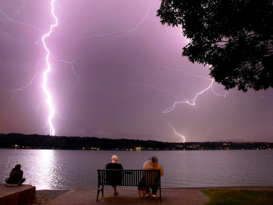 Storm watchers look at lightning strikes from Bachmann Park in Manette early Saturday. (LARRY STEAGALL / KITSAP SUN)