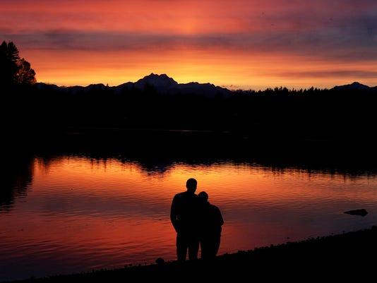 Justin Adrian and his wife Hillary of Bremerton watch the sunset together at the Pat Carey Vista in East Bremerton on Monday.  (LARRY STEAGALL / KITSAP SUN)