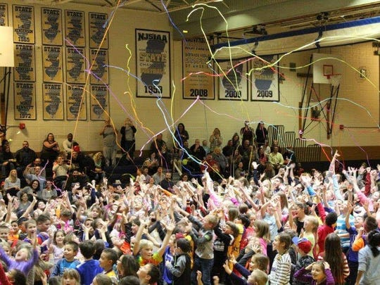 Students storm the court after the final buzzer at the Harlem Wizards Fundraiser.