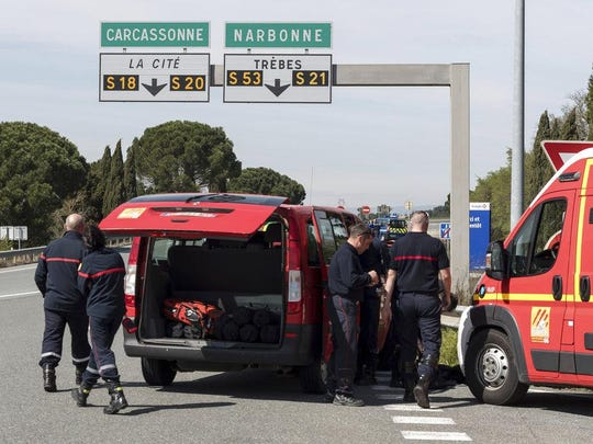 French police and firefighters secure the entrance of Trebes, southern France, where an armed man took hostages in a supermarket, Friday, March 23, 2018. French national police say two people have been killed and about a dozen wounded in a shooting and hostage-taking in a super market in southern France.