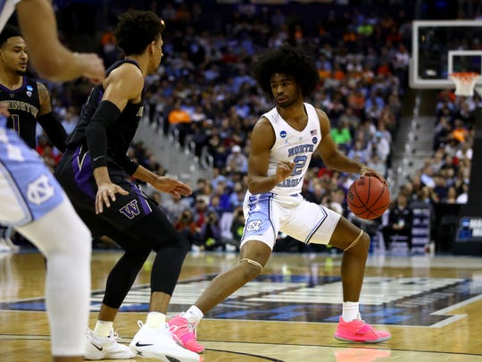 North Carolina guard Coby White (2) drives against Washington's David Crisp (1) in the second round of the NCAA Tournament at Nationwide Arena on March 24, 2019 in Columbus, Ohio.