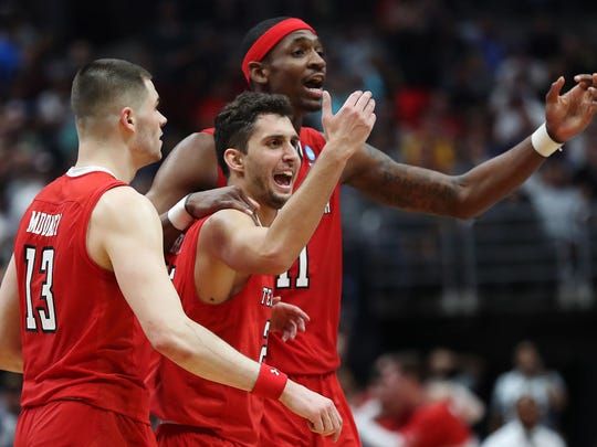 Tariq Owens (11), Davide Moretti (25) and Matt Mooney (13) of the Texas Tech Red Raiders celebrate a big play at the NCAA Tournament West Regional on Saturday. The Red Raiders knocked off 1-seed Gonzaga to earn a Final Four berth against Michigan State this weekend.