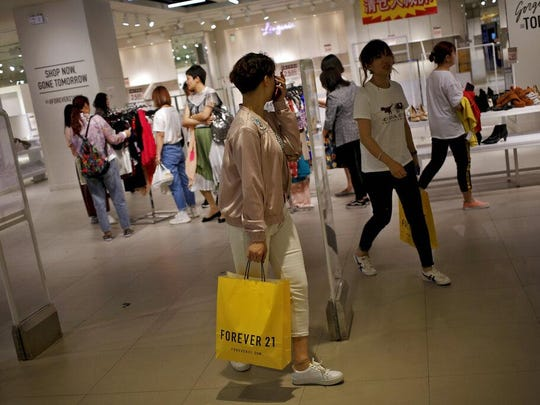 Chinese women carry paper bag of Forever 21, an American fast fashion retailer which is offering clearance discounts at a shopping mall after it pulled out from China's market, Tuesday in Beijing. China confirmed Tuesday its economy czar will go to Washington for trade talks despite fears he might cancel after President Donald Trump threatened to escalate a tariff war over Beijing's technology ambitions.