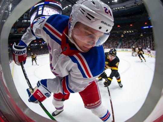 New York Rangers' Kaapo Kakko, front, of Finland, and Vancouver Canucks' Quinn Hughes vie for the puck during the first period of an NHL hockey game Saturday, Jan. 4, 2020, in Vancouver, British Columbia.