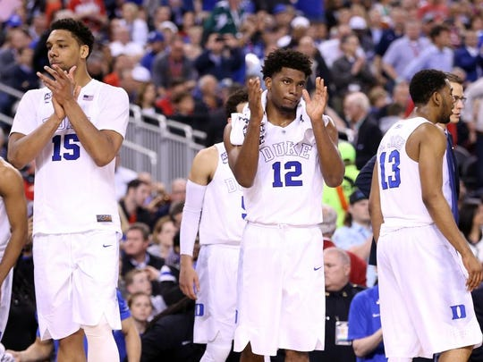 Jahlil Okafor (15) and Justise Winslow (12) of the Duke Blue Devils celebrate after defeating Michigan State during the NCAA Men's Final Four Semifinal at Lucas Oil Stadiumon Saturday in Indianapolis.