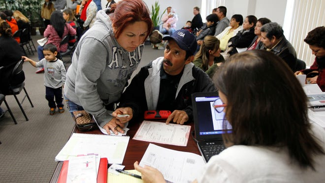 Jesus Rodriguez, center, and his wife Berta Salazar look over a problem with his documents while seeking help from Norma Canales Gomez Tuesday at the Mexican Consulate office in McAllen. Mexican citizens living in the United States continued preparing their paperwork for deferment from deportation Tuesday despite a U.S. Federal Court decision to temporarily block President Obama's executive action on immigration.