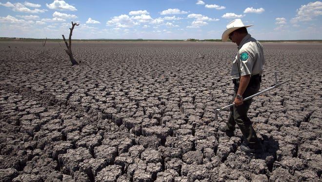 In this Wednesday, Aug. 3, 2011 file photo, Texas State Park police officer Thomas Bigham walks across the cracked lake bed of O.C. Fisher Lake in San Angelo, Texas. A new report says that some weather events like heat waves and droughts can be linked to climate change.