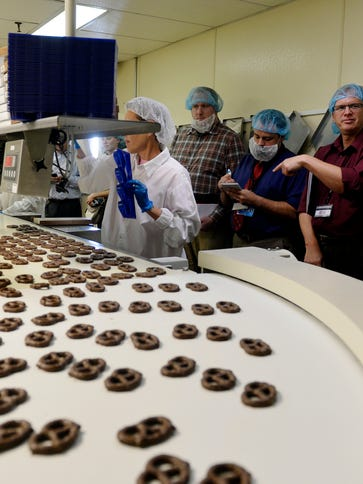 A group of visiting trade journalists watch cooled
