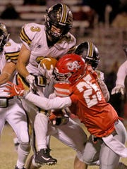 Holliday's Jack Pittman (25) tackles Henrietta's Mason Marchman (3) Friday, Oct. 27, 2017, in Holliday.
