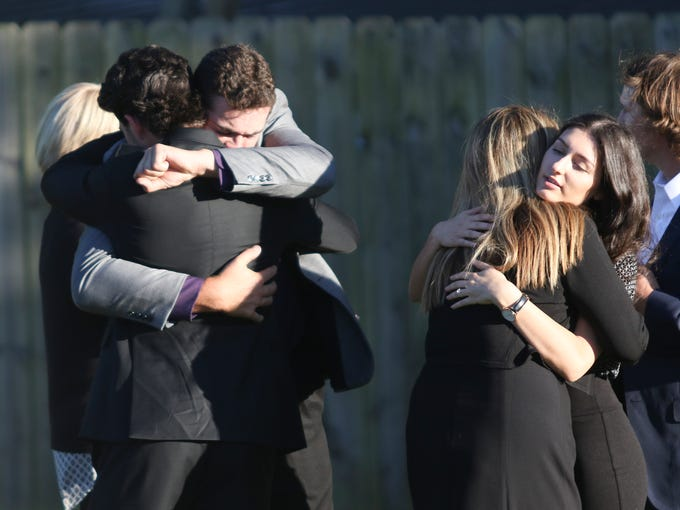 Mourners console each other after the graveside services