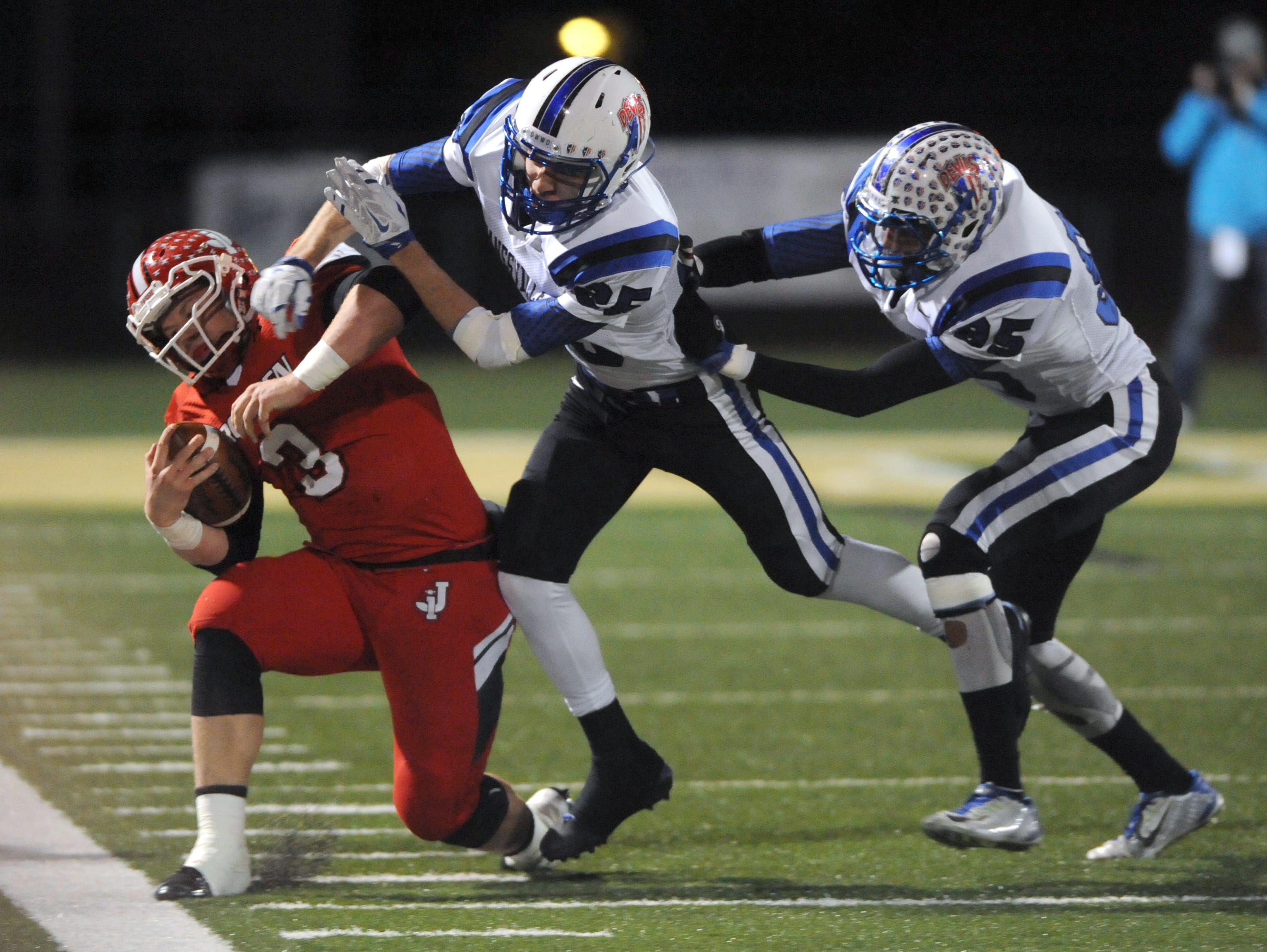 Zanesville's Dominic Stuchell and Javier Madinger-Rush knock Jackson's Hunter Sexton out of bounds Friday during the Blue Devils 38-21 regional finals victory in The Plains.