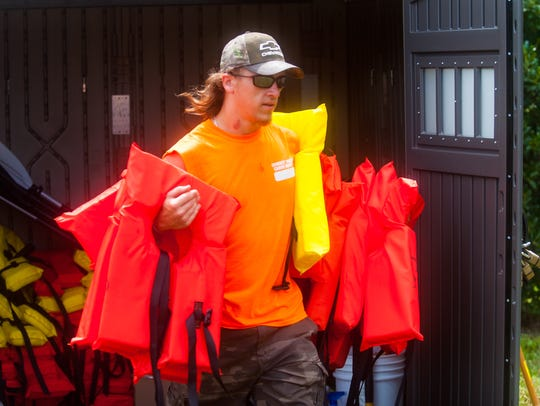 Michael Martin gathers life vests for Cowboy Mike's