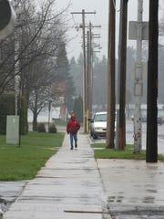 A woman walks along Edison Street in downtown Antigo, Wisconsin in the rain April 25, 2016.