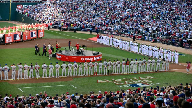 National League and American League players line up on the base lines before the 2014 MLB All Star Game at Target Field.