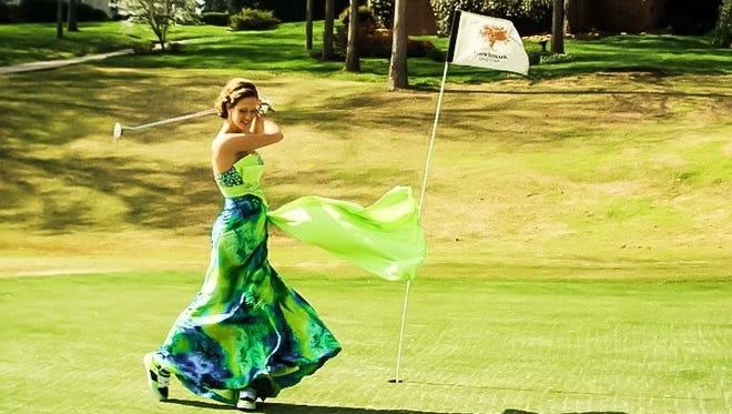 """Chelsea Henley said this is her favorite prom photo. It was taken at Avalon Golf Course before she went to Farrgut High School's prom. """"I have played golf for most of my life so it seemed normal to take a picture on the golf course, said Passmore in an email. I didn't plan on swinging a full club in my dress so I only brought my putter to take pictures with. The wind was crazy and as you can see, was blowing my dress around so I was goofing off when the photographer caught this shot."""""""
