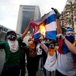 """A woman wearing a cap representing Venezuela's national flag, the SOS distress signal marked across her lips and painted black tears streaming down her face, looks into the camera during a demonstration in Caracas, Venezuela, Saturday, March 8, 2014. Venezuelans returned to the streets for the """"empty pots march"""" to highlight growing frustration with shortages of some everyday items."""