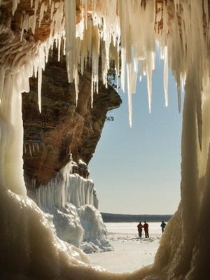 Frozen waves and water formed these large icicles that grace the ceiling of this red sandstone cliff as visitors are seen through the ice cave window along Lake Superior's south shore at the Apostle Islands National Lakeshore near Bayfield.