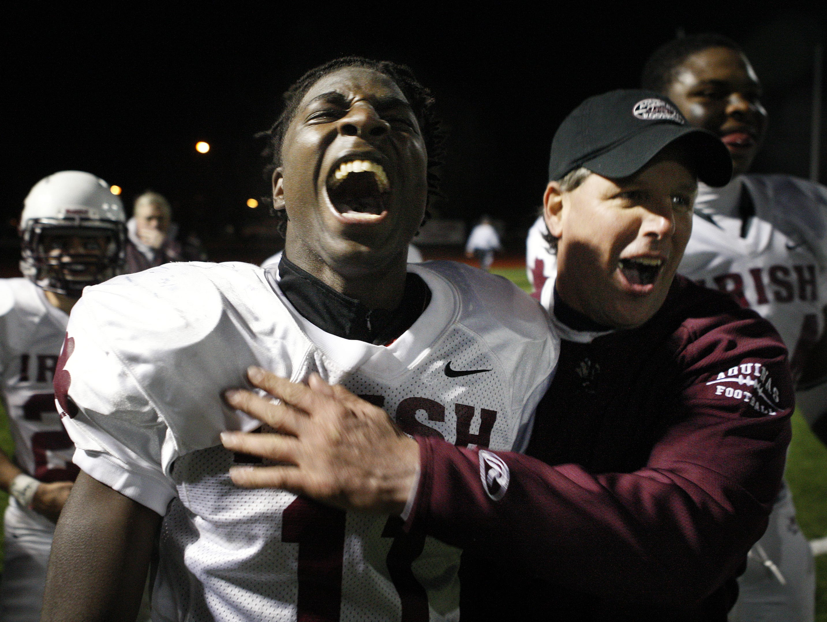 Aquinas' Jahmahl Pardner, left, lets out a scream while celebrating with coach Chris Battaglia after returning a punt 67 yards for a touchdown against Sweet Home during the 2010 Class A state regional.