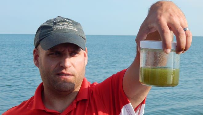 Tory Gabriel, Ohio Sea Grant fisheries outreach coordinator, holds a water sample containing microcystis — the type of blue-green algae that can produce toxins — taken near Rattlesnake Island in Lake Erie.