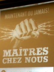 """An energetic call to self-sufficiency in Québec (""""Now or never! Our own masters""""), seen in this projected image of a Liberal Party political poster from 1962."""