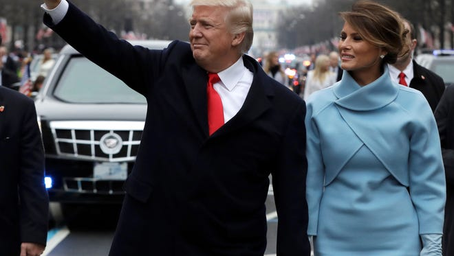 President Donald Trump waves as he walks with first lady Melania Trump during the inauguration parade on Pennsylvania Avenue in Washington on Jan. 20, 2017. Big money from billionaires, corporations and a roster of NFL owners poured into Donald Trump''s inaugural committee in record-shattering amounts.