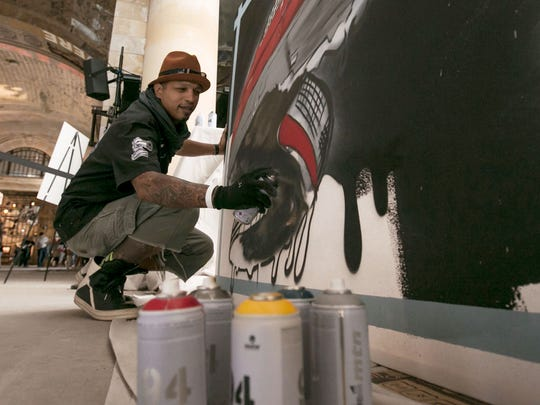 "Antonio ""Shades"" Agee of Detroit spray paints artwork that will be on display while working inside Michigan Central Station in Detroit during an open house put on by Ford Motor Company on Friday, June 22, 2018."