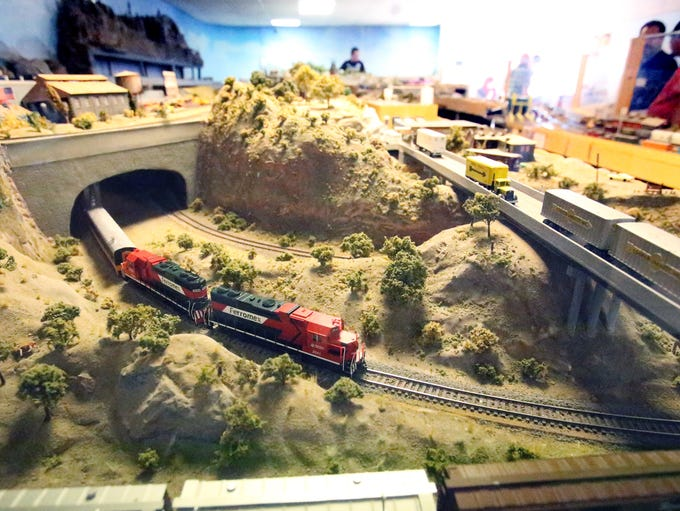 An HO scale Ferromex freight train emerges from a tunnel