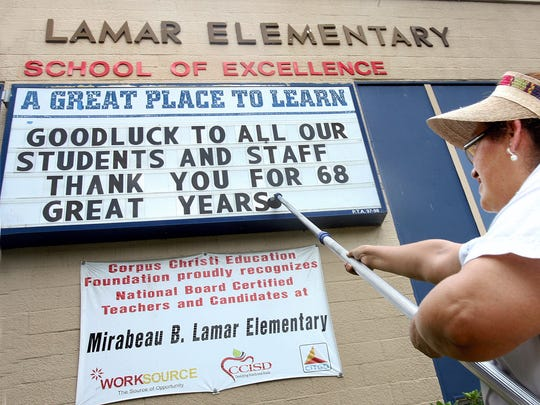 Lamar elementary school head custodian, Marivel Viera, puts up letters to the school marquee on 6/3/2010. The school opened in 1941 and closed in 2010. It reopened as the Lamar Community Service and Education Center.