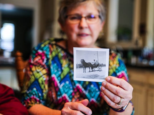 Becky Bookter holds up a photo of herself on a buggy she rode in the rodeo parade Wednesday, Jan. 31, 2018, at their San Angelo home.