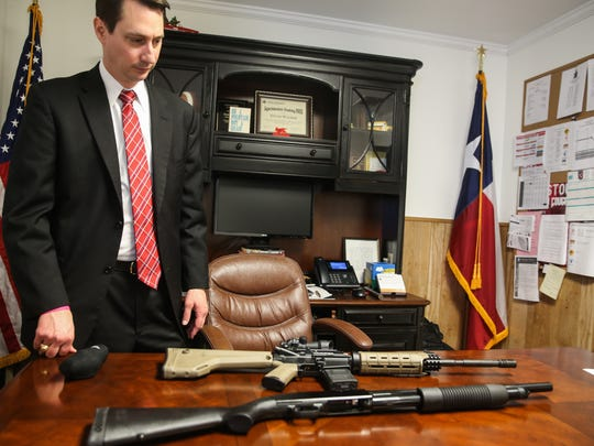 David Walker, Christoval superintendent, lays rifles on his desk Monday, Feb. 26, 2018, in his office.