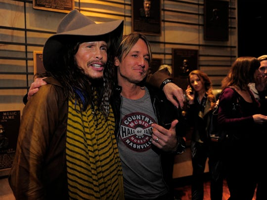 Steven Tyler and Keith Urban greet each other at the Country Music Hall of Fame on Dec. 1 in Nashville.