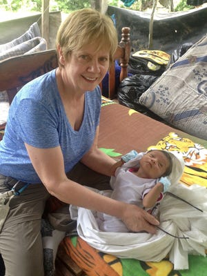 Auburn pediatrician Nancy DeTora is shown here caring for a Kichwa baby in a rainforest hut.