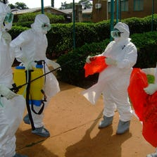 Officials from the World Health Organization wear protective clothing on July 28, 2012 as they prepare to enter Kagadi Hospital in Kibale District, about 200 kilometres from Kampala, where an outbreak of Ebola virus started. The World Health Organization has said there is no need to panic and that everything has been done to contain the situation.
