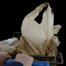 A shopper leaves a supermarket with groceries in plastic bags