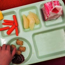 A student reaches for a tater tot during lunch period.