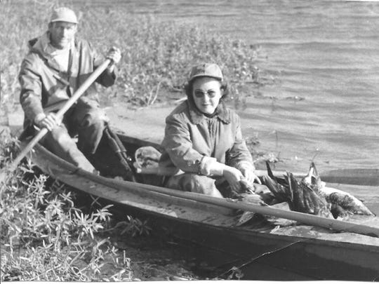 Grits and Mary Gresham are shown riding in a pirogue in the Louisiana marsh while hunting ducks in a year not documented but believed to be in the late 1940s.