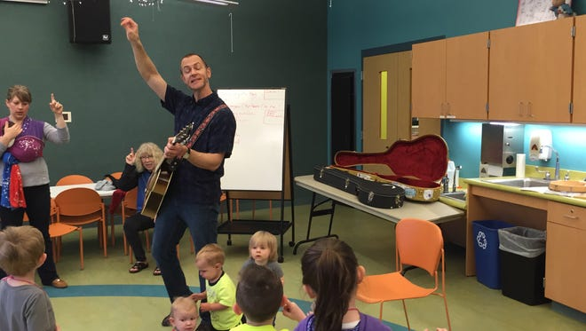 William E. Durr Branch Children's Services Coordinator Joel Caithamer performs a song for attendees of the Preschool Storytime.