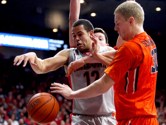 Arizona forward Ryan Anderson (12) and Oregon State forward Olaf Schaftenaar vie for the loose ball during the second half of an NCAA college basketball game Saturday, Jan. 30, 2016, in Tucson, Ariz. Arizona defeated Oregon State 80-63.