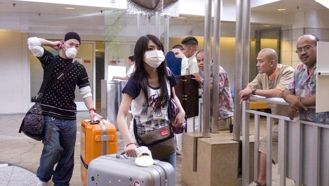 Travelers arriving at the A.B. Won Pat Guam International Airport on a flight from Japan in April 2009 are seen wearing protective masks. At that time, media coverage was focused on the H1N1 flu pandemic, or swine flu.