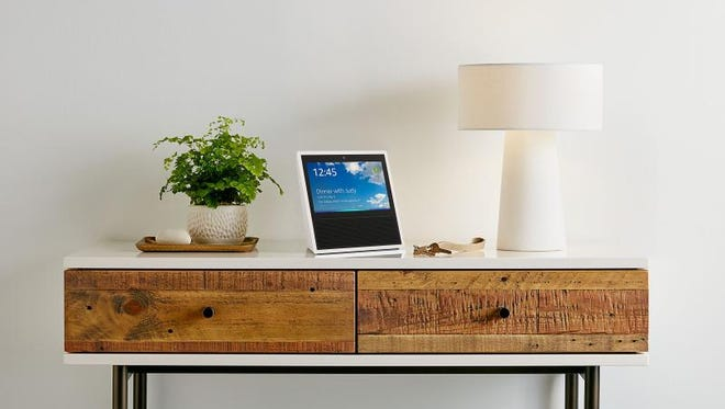 """This photo provided by Amazon shows an Amazon Echo Show on display in a living room setting. Amazon is giving its voice-enabled Echo speaker a touch screen and video-calling capabilities as it competes with Google's efforts at bringing """"smarts"""" to the home. The new device, called Echo Show, goes on sale on June 28, 2017. Amazon says it's also bringing calling and messaging features to its existing Echo and Echo Dot devices and the Alexa app for phones."""